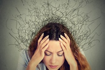 Woman with head in hands dealing with anxiety